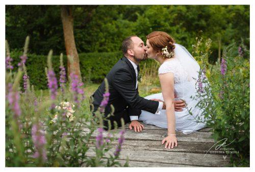 ženich líbá nevěstu mezi květinami svatební fotograf