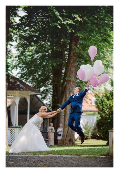 svatba Villa Voyta ženich letí s balónky a nevěsta ho drží svatební fotograf