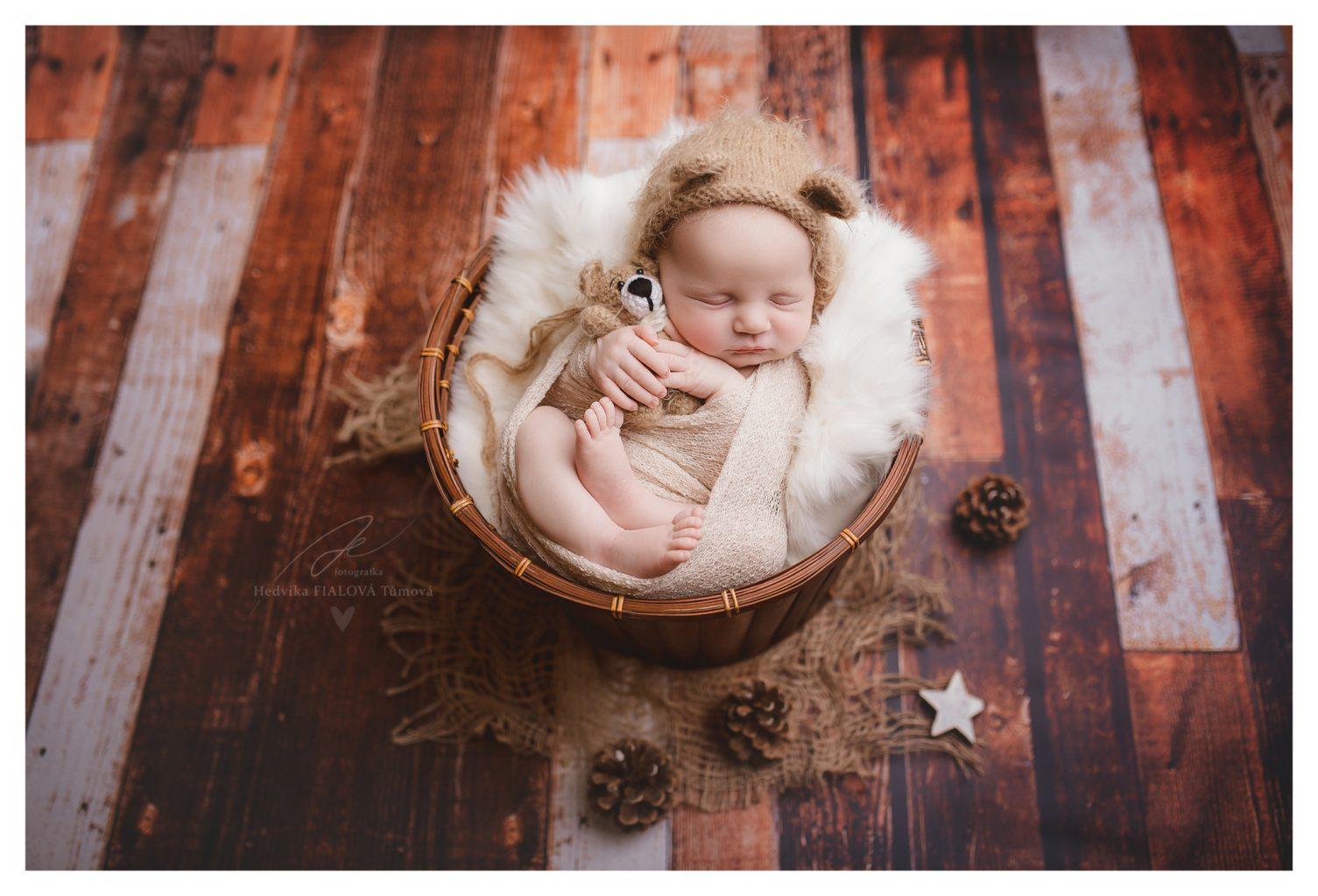 newborn miminko v košíku s čepičkou a medvídkem